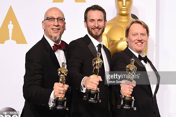 Producer Roy Conli and directors Chris Williams and Don Hall pose with their award in the press room during the 87th Annual Academy Awards at Loews...