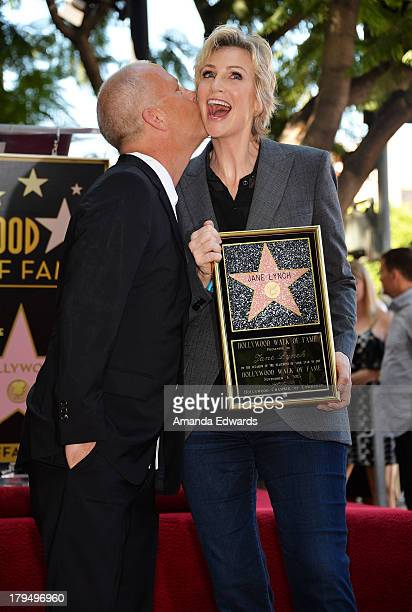 Producer Ryan Murphy kisses actress Jane Lynch as she is honored on The Hollywood Walk of Fame on September 4 2013 in Hollywood California