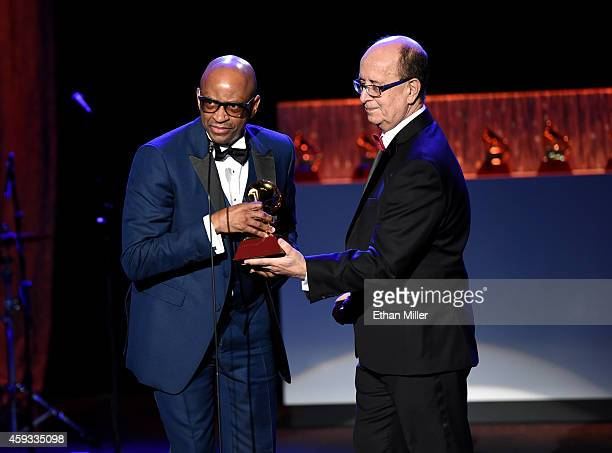 Producer Sergio George accepts the award for Producer Of The Year from composer Antonio Adolfo onstage during the 15th annual Latin GRAMMY Awards at...