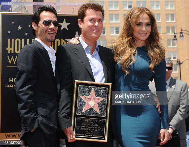 Producer Simon Fuller stands with singer Mark Anthony and his wife singer/actress Jennifer Lopez after he unveilled his star at the ceremony honoring...