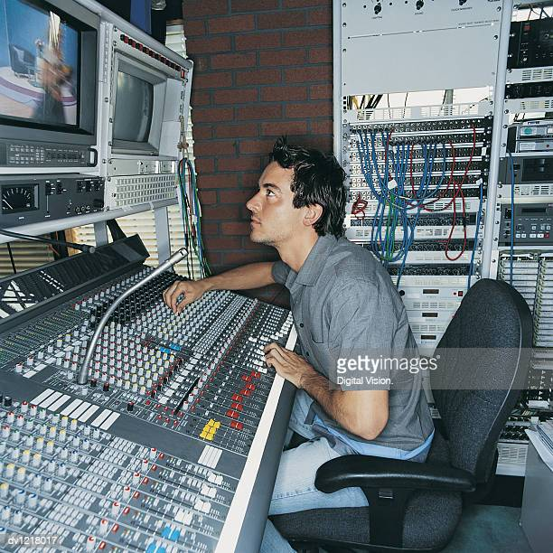 Producer Sitting at a Control Panel in a TV Studio