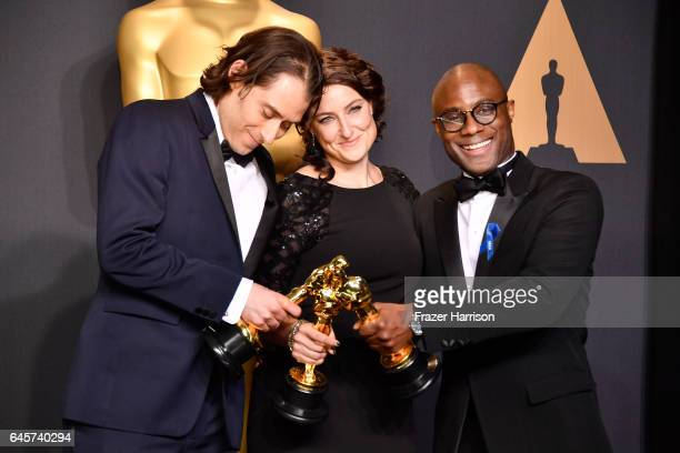 Producers Jeremy Kleiner and Adele Romanski winners of the award for Best Picture for 'Moonlight' pose with filmmaker Barry Jenkins in the press room...