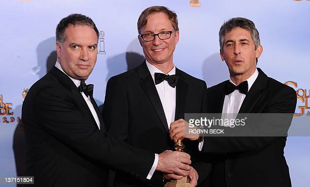 Producers Jim Taylor Jim Burke and writer/Director Alexander Payne Winners for Best Motion Picture Drama The Descendants pose with the trophy at the...