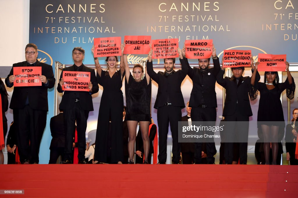 Producers Thiago Macedo Correia, Ricardo Alves Jr, Isabella Nader, directors Renee Nader Messora, Joao Salaviza, guest, Ihjac Kraho and Koto Kraho from the film 'The Dead And The Others' hold signs in protest as they attend the screening of 'Dogman' during the 71st annual Cannes Film Festival at Palais des Festivals on May 16, 2018 in Cannes, France.
