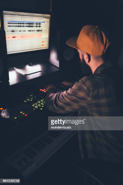 dj producing music using professional audio equipment in music studio - post-production stock pictures, royalty-free photos & images