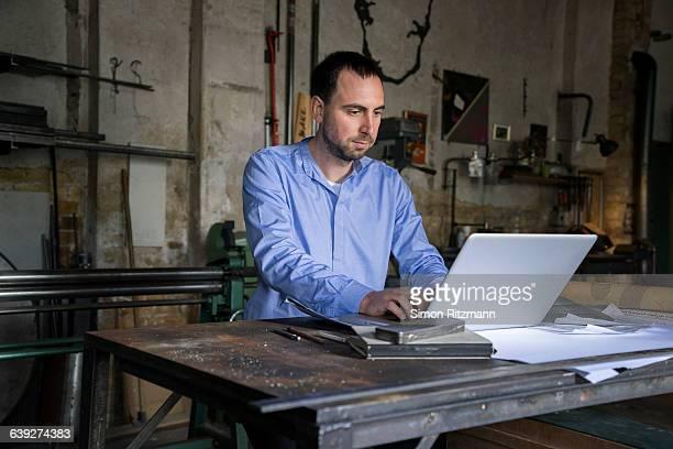 Product designer using laptop in workshop