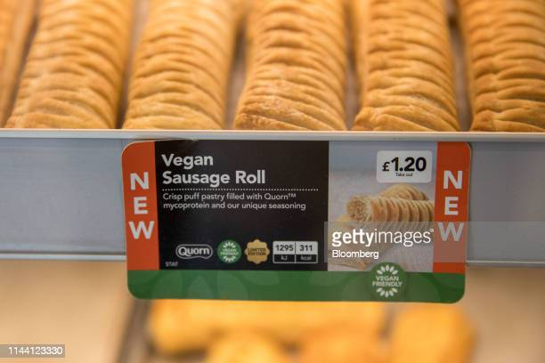 Product information sign sits in a counter display for vegan sausage rolls at a Greggs Plc sandwich chain outlet in London, U.K., on Wednesday, May....