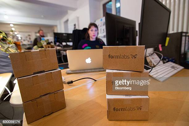 Product sample boxes sit on a desk as employees work inside the offices of 3D printing and design company Formlabs GmbH in Berlin Germany on Tuesday...