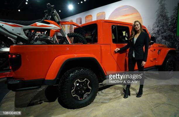 A product specialist stands next to a Jeep at the 2019 North American International Auto Show January 15 2019 at the Cobo Center in Detroit Michigan...