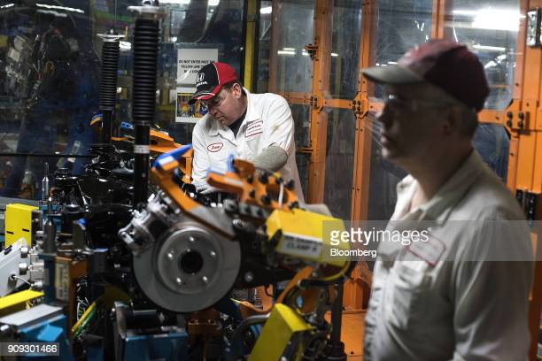 A production associate adds parts to the rear suspension of a 2018 Honda Accord vehicle during production at the Honda of America Manufacturing Inc...
