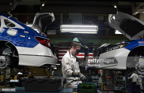 A production associate adjusts his hat while working between 2018 Honda Accord vehicles during production at the Honda of America Manufacturing Inc...