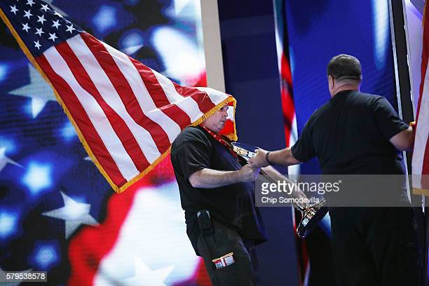 Production crew members move U.S. Flags on the stage inside the Wells Fargo Arena the day before the start of the Democratic National Convention July...