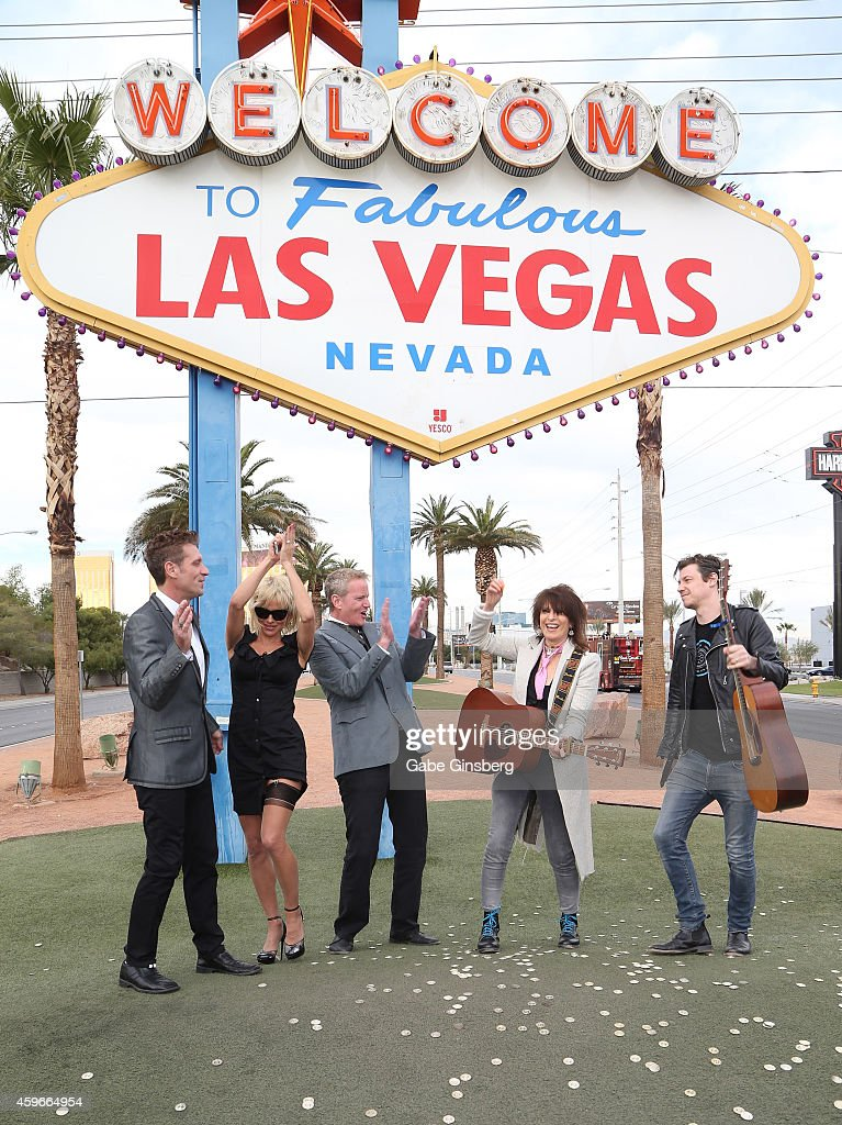 Production designer Jack Ryan, actress Pamela Anderson and Senior Vice President of media campaigns for PETA Dan Mathews celebrate as musician Chrissie Hynde of The Pretenders and a guest perform during the wedding of Dan Mathews and Jack Ryan at the Welcome to Fabulous Las Vegas sign on November 27, 2014 in Las Vegas, Nevada.