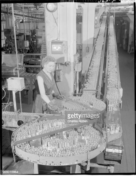 Production line of batteries A worker tends to a production line of batteries at the East Alton Works plant Location East Alton Illinois USA circa...