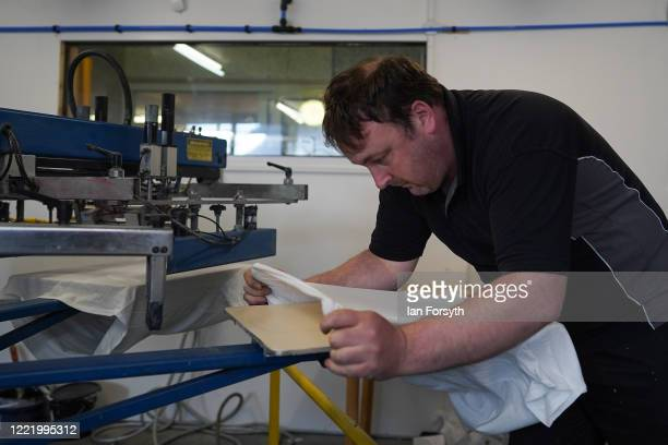 Production Manager Craig Swanston slides a blank t-shirt onto a screen printing machine as he produces NHS branded t-shirts on April 30, 2020 in...