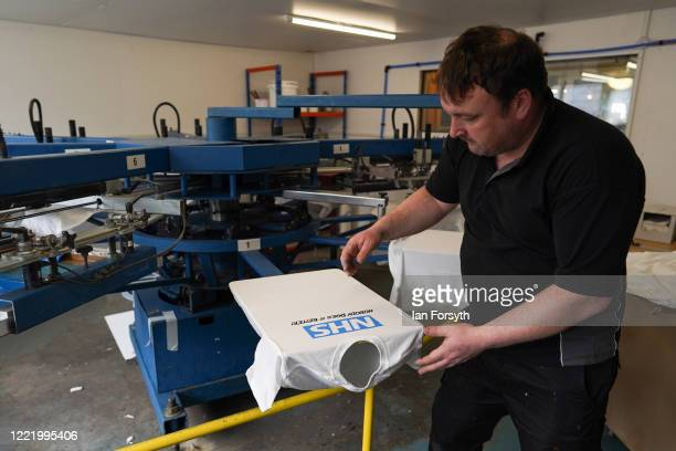Production Manager Craig Swanston works a screen printing machine as he produces NHS branded t-shirts on April 30, 2020 in Hartlepool, England. Mr...