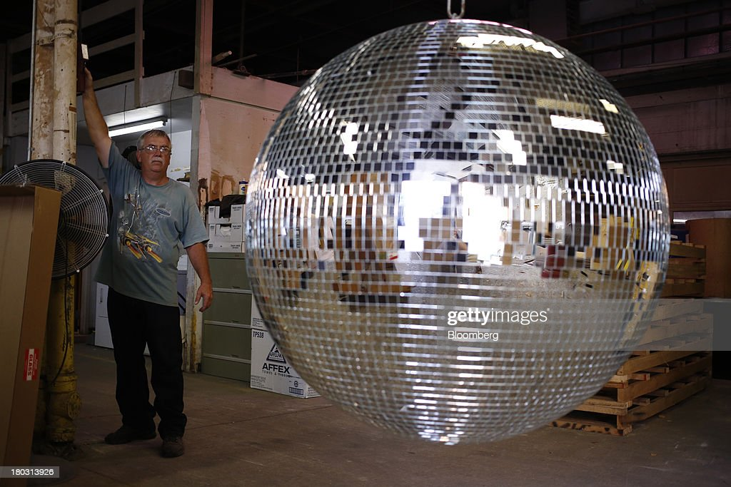 Production manager Ernie Miller hoists a four foot disco ball during a demonstration at the Omega National Products manufacturing facility in Louisville, Kentucky, U.S., on Tuesday, Sept. 10, 2013. The U.S. Federal Reserve is scheduled to release industrial production figures on Sept. 16. Photographer: Luke Sharrett/Bloomberg via Getty Images