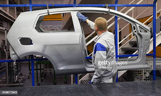 Production of the VW Golf VII in Wolfsburg a worker checks parts of doors in the pressing plant