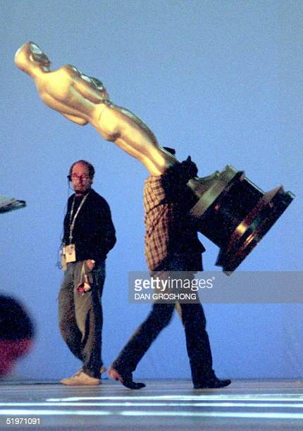 A production worker carries a giant Oscar across the stage 24 March during preperations for the 67th Annual Academy Awards which will take place...