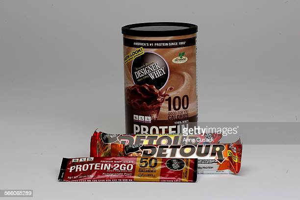 Products made with whey protein made by Designer Whey including top to bottom powder drink mix Detour bars and Protein to Go photographed in the...