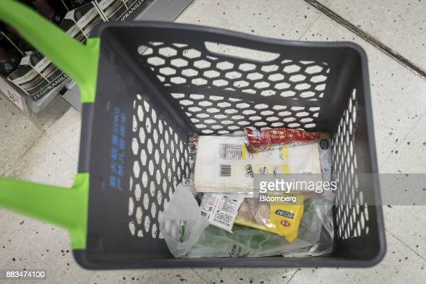 Products sit inside a shopping basket as an employee fulfills an electronic order in a WalMart Stores Inc miniwarehouse for the company's onehour...