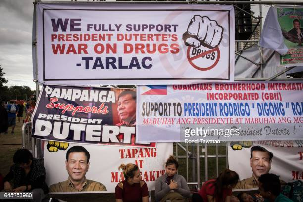 ProDuterte supporters rest before tarpaulins expressing support for Philippine president Rodrigo Duterte's antidrug campaign before a vigil rally...