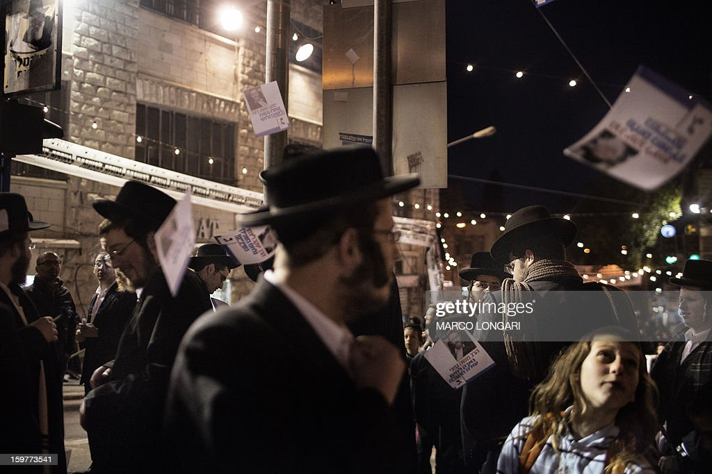 Pro-election flyers are thrown among Ultra Orthodox Jews belonging to the Satmar Hasidic group headed by Satmar Rebbe of Williamsburg, Rabbi Zalman Leib Teitelbaum, during an anti-election rally in the conservative Mea Shearim neighbourhood of Jerusalem on January 20, 2013, two days before nationwide voting for the general election gets underway on January 22.
