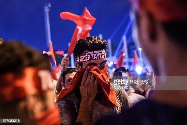 Pro-Erdogan supporter drys his eye with a piece of fabric during a rally at Taksim square in Istanbul on July 18, 2016 following the military failed...