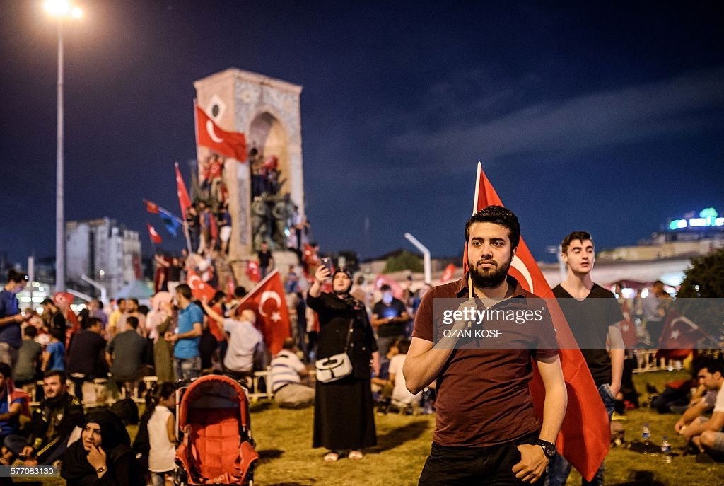 Pro-Erdogan supporter holds a Turkish national flag during a rally at Taksim square in Istanbul on July 18, 2016 following the military failed coup attempt of July 15. stands by a woman takling a picture with her cell-phonmeTurkish security forces on July 18 carried out new raids against suspected plotters of the botched coup against the rule of President Recep Tayyip Erdogan, as international concern grew over the scale of the crackdown. Thousands of pro-Erdogan supporters waving Turkish flags filled the main Kizilay Square in Ankara while similar scenes were seen in Taksim Square in Istanbul, AFP photographers said. / AFP / OZAN