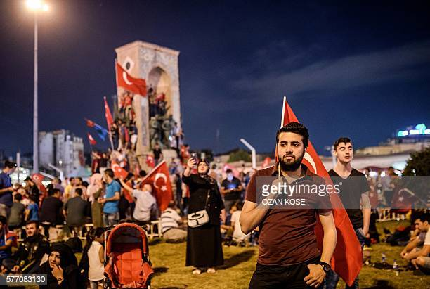 Pro-Erdogan supporter holds a Turkish national flag during a rally at Taksim square in Istanbul on July 18, 2016 following the military failed coup...