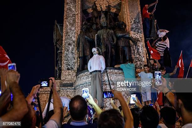 Pro-Erdogan supporters hold an effigy of US-based preacher Fethullah Gulen hunged by a noose during a rally at Taksim square in Istanbul on July 18,...