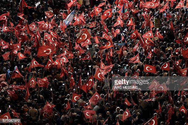 ProErdogan supporters hold Turkish national flags during a rally at Taksim square in Istanbul on July 18 2016 following the military failed coup...