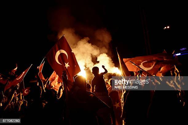 TOPSHOT ProErdogan supporters wave Turkish national flags during a rally at Taksim square in Istanbul on July 18 2016 following the military failed...