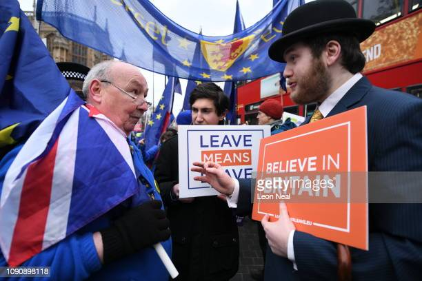 ProEU and proBrexit protestors discuss the vote and ongoing political processes as they demonstrate near to the Houses of Parliament on January 29...