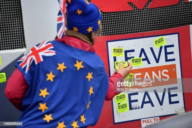 ProEU antiBrexit demonstrators afix stickers to a bus operated by the proBrexit Leave Means Leave protestgroup as they porest opposite the Houses of...