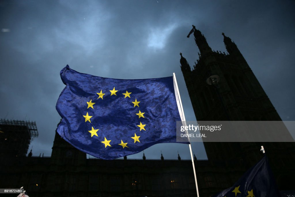 Pro-EU anti-Brexit demonstrators wave an EU flag outside the Houses of Parliament in central London on December 13, 2017 as MPs debate a proposed amendment to the EU Withdrawl Bill. British Prime Minister Theresa May was December 13 facing a rebellion from her own MPs over whether parliament will have a 'meaningful vote' on the final Brexit deal in what would be a damaging defeat. / AFP PHOTO / Daniel LEAL