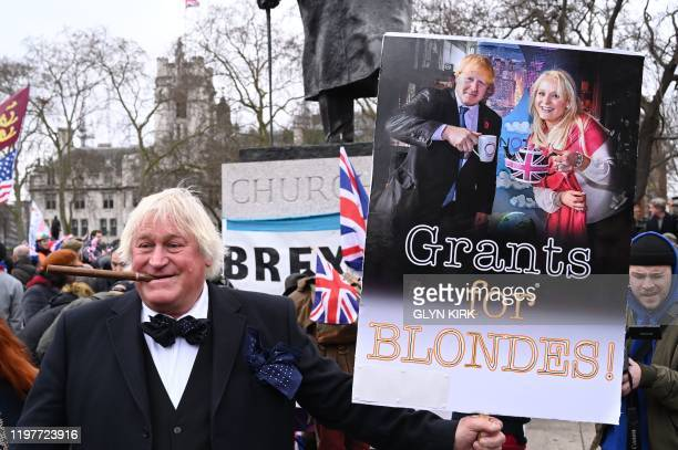 A proEU antiBrexit protester holds up a placard showing Britain's Prime Minister Boris Johnson and US businesswoman Jennifer Arcuri in Parliament...