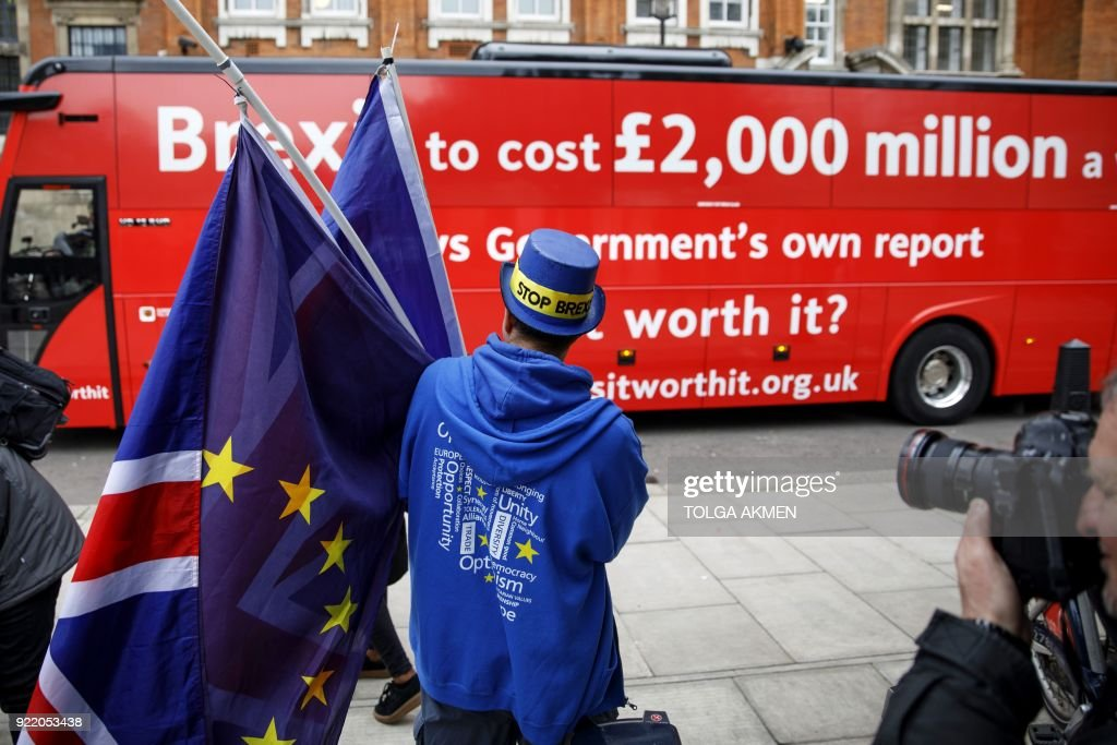 TOPSHOT - A pro-EU campaigner watches as the Brexit Facts Bus, rolled out by European Union advocates as they kick off a new initiative against Brexit, leaves College Green in central London on February 21, 2018. European Union advocates kicked off a new campaign against Brexit on February 21, 2018, unveiling a coach emblazoned with dire economic warnings in a strategy echoing the 2016 'Leave' campaign's infamous bus slogan tactic. / AFP PHOTO / Tolga Akmen