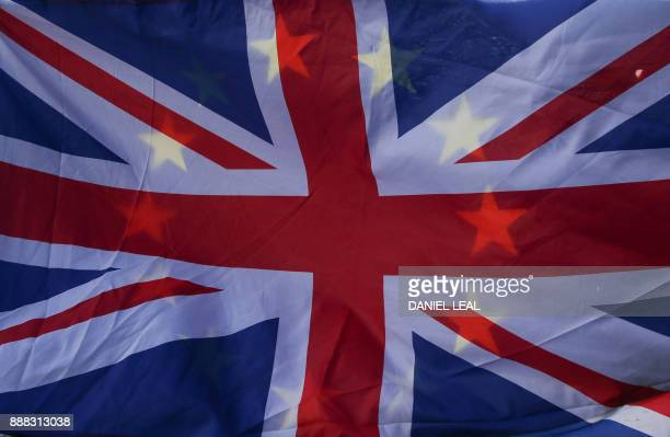 ProEU demonstrators fly a Union flag and an EU flag outside of the Houses of Parliament in Westminster central London on December 8 2017 after a...