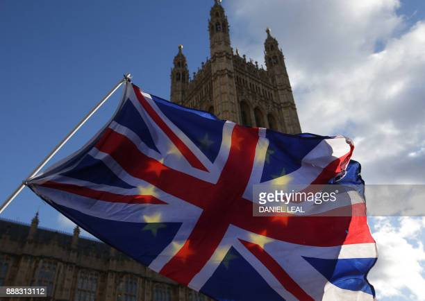 ProEU demonstrators flying a Union flag and an EU flag outside of the Houses of Parliament in Westminster central London on December 8 2017 after a...