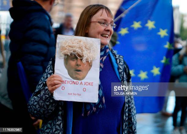 A proEU protester holds up a placard mocking Britain's Prime Minister Boris Johnson beside the Houses of Parliament in Westminster central London on...