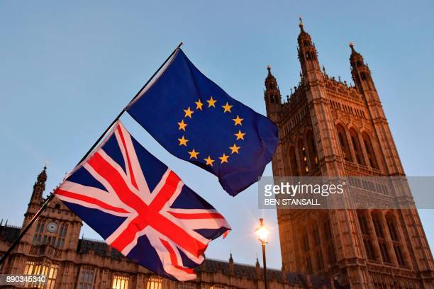 ProEU protesters wave EU and Union Flags outside the Houses of Parliament in central London on December 11 2017 as Britain's Prime Minister Theresa...