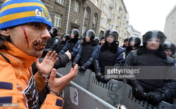A proEuropean activist with a 'sewn up' mouth stands with symbolic handcuffs opposite riot policemen during an opposition rally outside the...