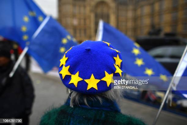 A proEuropean Union antiBrexit demonstrator wears an EU flag themed beret while waving EU flags they protest outside the Houses of Parliament in...