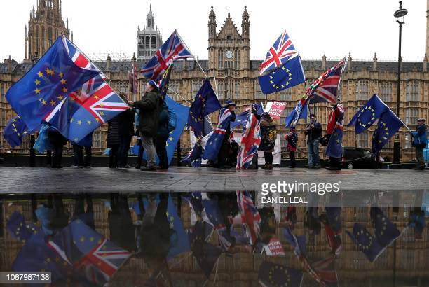 ProEuropean Union antiBrexit demonstrators wave Union and EU flags as they protest opposite the Houses of Parliament in London on December 3 2018...