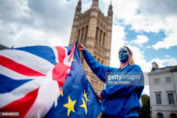 ProEuropean Union protester holds Union and European flags in front of the Victoria Tower at The Palace of Westminster in central London on September...