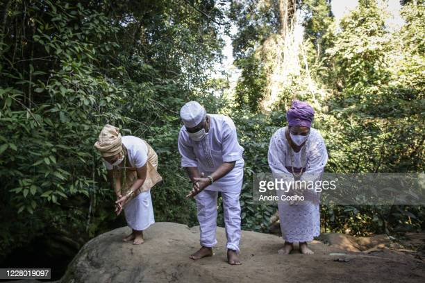 Prof. Dr. Babalawô Ivanir dos Santos and devotees Monique Osunyoyin Ifayemisi and Eloisa Iemanjá Ifayoyin wear protective masks while sing a song in...