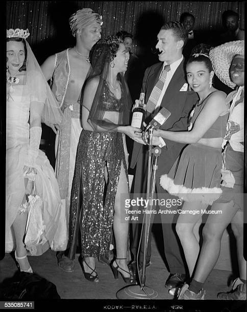 Profanity Club members wearing Halloween costumes including 'Sonny' Brooks in center woman wearing genie costume and holding liquor bottle and Walt...