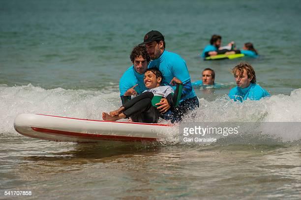 Profesional surfer Aritz Aranburu member of Kind Surf NGO help some kids to surf on the International Surf Day on June 20 2016 in San Sebastian Spain...