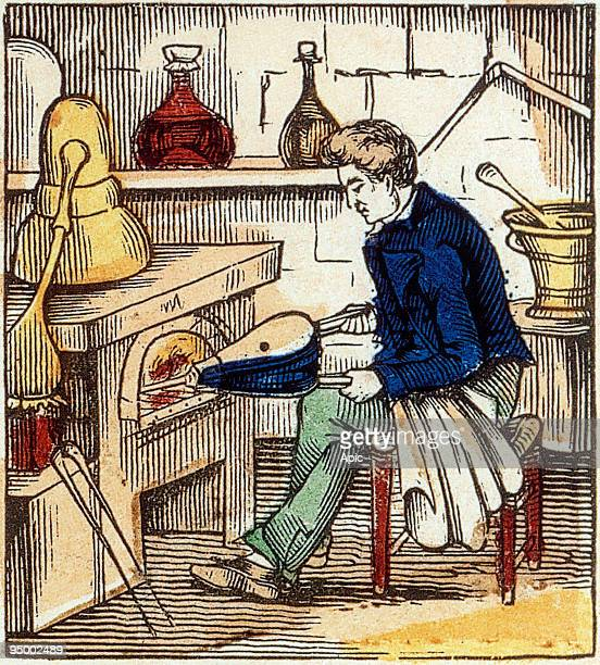 distiller stirring fire with bellows for his alembic engraving from 'Alphabet des Arts et Metiers' France late 19th century